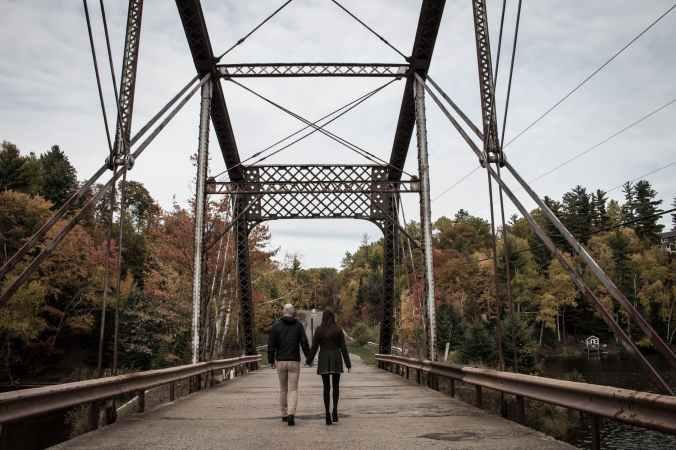 couple walking on gray bridge at daytime