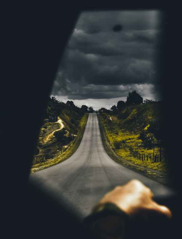 highway near trees under cloudy sky