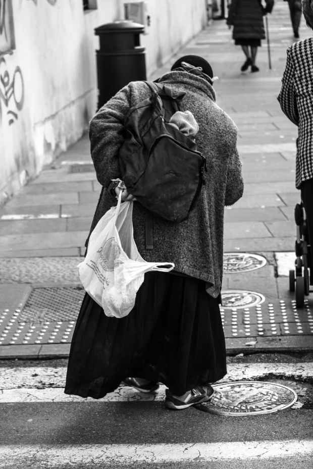 man holding plastic bag with coat