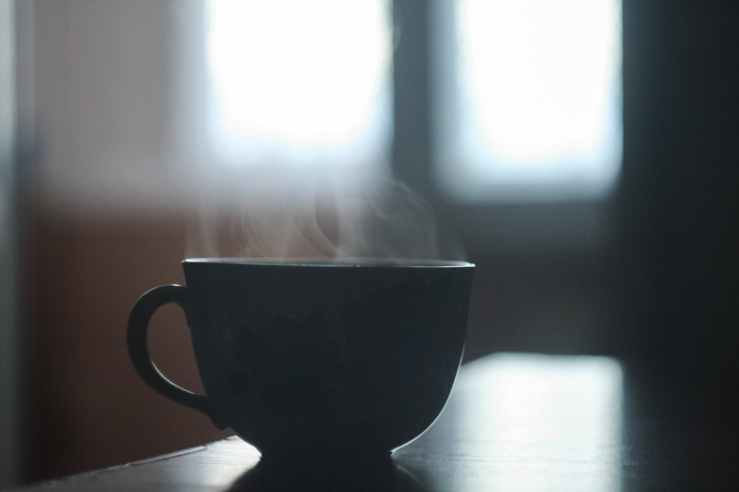 black ceramic cup with smoke above
