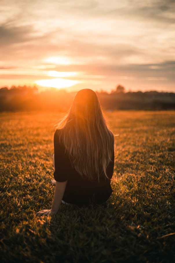 woman in black shirt sitting on grass during sunset