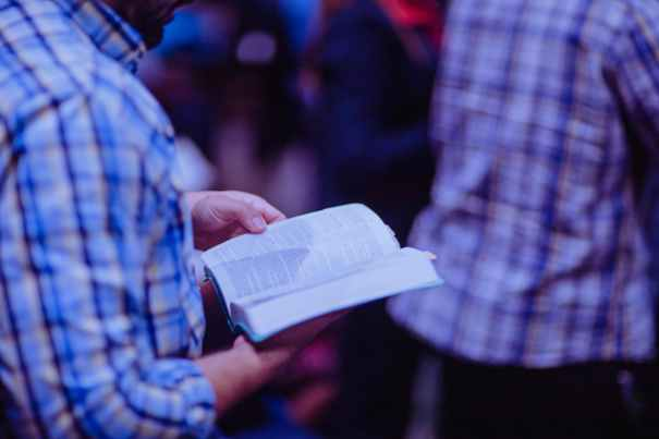 person reading the bible while standing