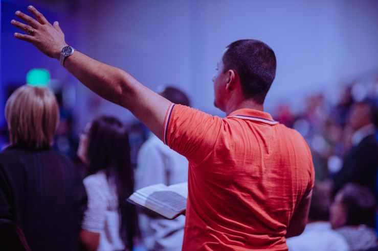 man raising his left hand